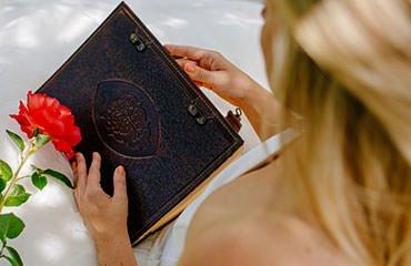 Braunes Hochzeitsbuch mit eingeprägtem Baum liegt auf den Knien einer Braut, daneben eine Rose