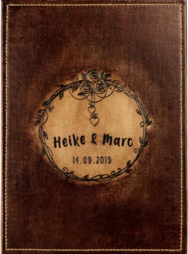 Personalisiertes Gästebuch mit einem Blumenkranz in dem die Namen stehen